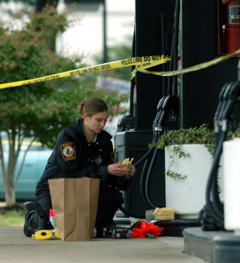 Henrico County, Va., police arrested two possible suspects in connection to the sniper shooting of a 37-year-old man outside a Ponderosa restaurant in Ashland, Va., last Monday. Jennifer Strano, of the Henrico County Police forensic unit, gathers materials used during her investigation at the Exxon gas station at the corner of Parham Road and Board Street in Richmond, Va. (Kenneth K. Lam/Baltimore Sun)