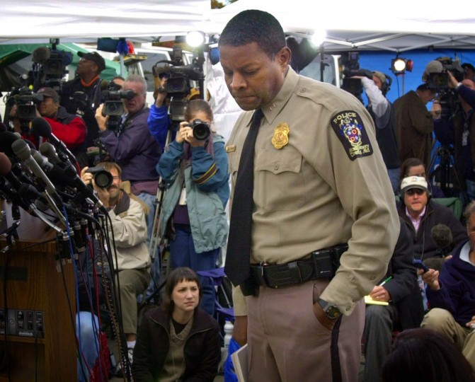 Appearing grim, Montgomery County Police Chief Charles Moose stops for a moment before continuing to the podium as members of the news media train their still and video cameras on him as he prepares to announce the fatal shooting of a bus driver as he stood on the steps of the bus he was driving Mon., Oct. 22, 2002. Fears are growing that a sniper may have struck again as police attempt to gather evidence following the murder early this morning. (Karl Merton Ferron/Baltimore Sun)