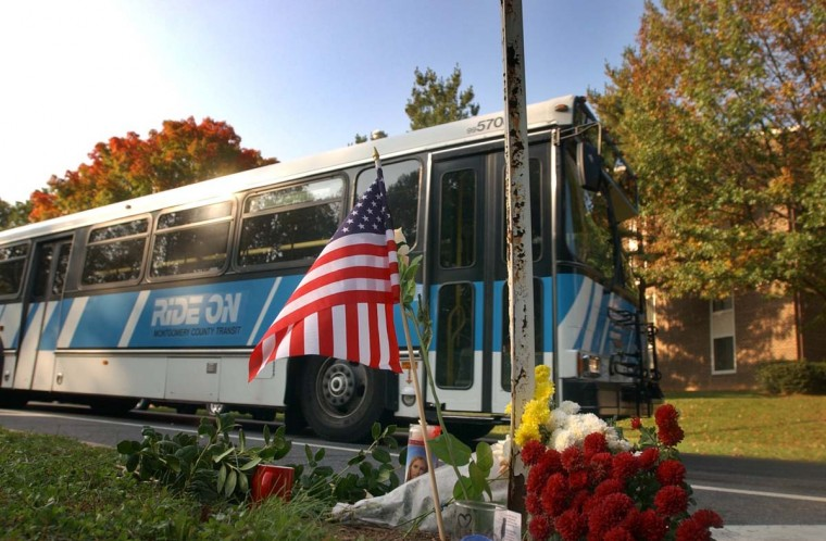 """A Ride On bus drives past a bus stop where a makeshift memorial rests Wed., Oct. 23, 2002, one day after commuter bus driver Conrad Johnson was slain there by a sniper. Montgomery County Police Chief Charles Moose, who quoted a postscript believed to be written by the sniper outlining a threat to children says the police """"have not been able to assure anyone their safety."""" (Karl Merton Ferron/Baltimore Sun)"""