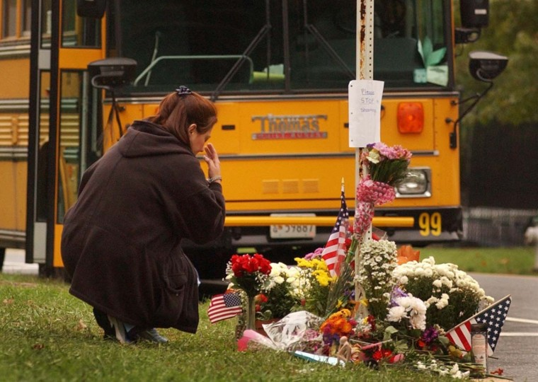 School bus driver Carolina Salas, of Aspen Hill, crosses herself as she visits an impromptu shrine where the sniper's last murder was committed. People were making their way back out into the world on news of the sniper's arrest. Her husband is also a (Ride-On) bus driver. (David Hobby/Baltimore Sun)