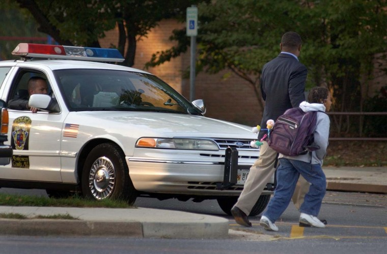 Government Contractor Kedn Jenkins, who has a flexible work schedule, escorts his daughter, 4th grade student Nicole Jenkins, 8 past a Montgomery County Police cruiser towards Strathmore Elementary School Wed., Oct. 23, 2002, one day after commuter bus driver Conrad Johnson was slain by an unidentified person just hundreds of yards from the site. (Karl Merton Ferron/Baltimore Sun)