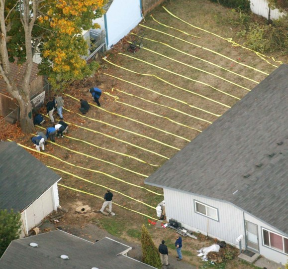 Investigators comb the yard of a Tacoma, Wash., home Thursday, Oct. 23, 2002, looking for evidence with a possible connection to the Washington, D.C. sniper shootings. The search for the serial sniper jumped across the country Wednesday as FBI agents converged on a home in Tacoma. A U.S. official in Washington said authorities were looking for two ``people of interest,'' one of them formerly connected to Fort Lewis, an Army base south of Tacoma. (Seattle Post-Intelligencer, Mike Urban)