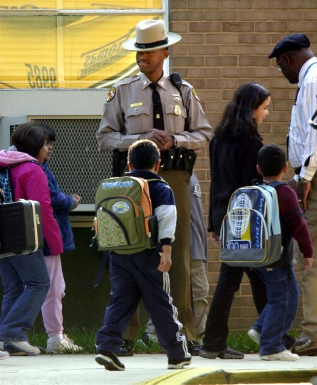 A Maryland State Trooper watches over children leaving school in Montgomery County, Maryland October 23, 2002. Police recently revealed that the Washington, DC area sniper has threatened children in a letter left a shooting scene. (Brian Snyder/Reuters photo)