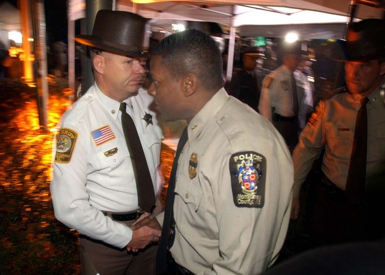Montgomery County police chief Charles Moose, right, is greeted by handshake by Sheriff Ronald Knight, of Spotsylvania Sheriff's Office, after a press conference , which announced that two suspects have been apprehended in connection to the serial sniper investigation. (Kenneth K. Lam/Baltimore Sun)
