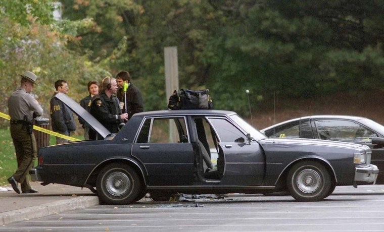 The car that John Muhammad and his stepson were in when Police surprised them at a rest stop along Route 70 near Myersville, Maryland sits surrounded by law enforcement officers October 24, 2002. Muhammad was picked up in relation to the Washington area sniper case. (Brendan McDermid/Reuters photo)