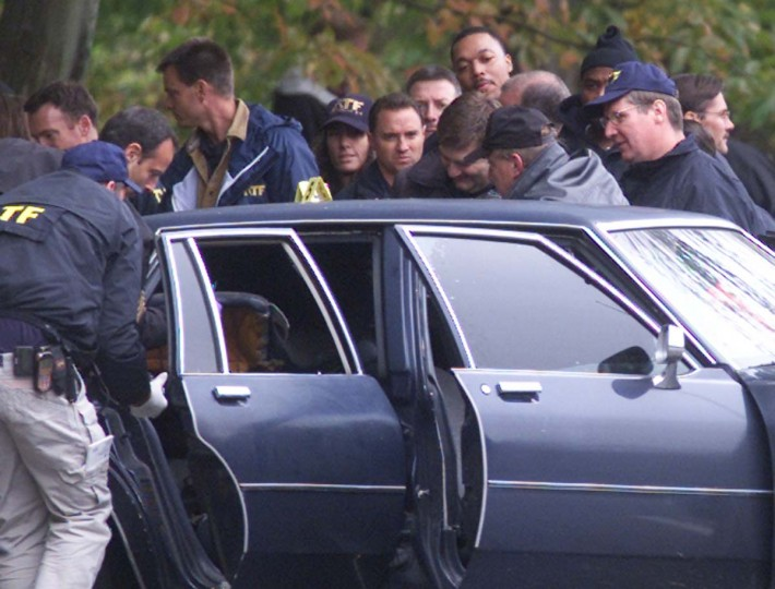 Law enforcement officers hold an item after lifting up the backseat of the car which John Allen Muhammad and John Lee Malvo were in when police arrested them at a rest stop near Myersville, Maryland October 24, 2002. Former U.S. soldier John Allen Muhammad, a Gulf War veteran, and John Lee Malvo, were arrested at the rest stop in rural Maryland early Thursday in the hunt for suspects in 10 sniper-style slayings in the Washington, D.C., area. (Brendan McDermid/Reuters photo)