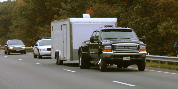 A caravan of police vehicles escorts a truck and trailer transporting the suspects vehicle which was discovered in Myersville, MD, after two men were arrested in connection with the sniper attacks. ( John Makely/Baltimore Sun)