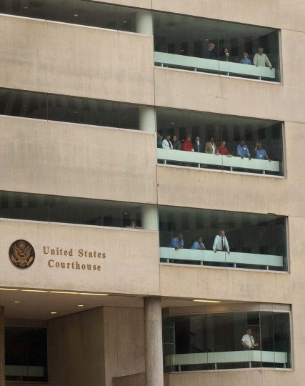 People look out the windows of the Garmatz Federal Courthouse while waiting for the sniper suspects to arrive. (Lloyd Fox/Baltimore Sun)