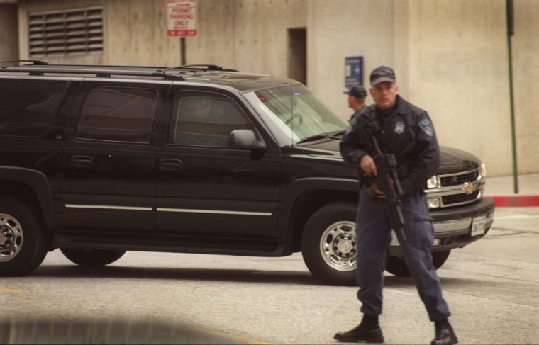 A Baltimore City police officer stands guard at the entrance of the Garmatz Federal Courthouse as a Chevy Blazer carrying law enforcement officers arrives in a hurry with an entourage of other vehicles carrying suspects that may be associated with the D.C. area sniper shootings Thursday, Oct. 24, 2002, in Baltimore, MD. (Glenn Fawcett/Baltimore Sun)