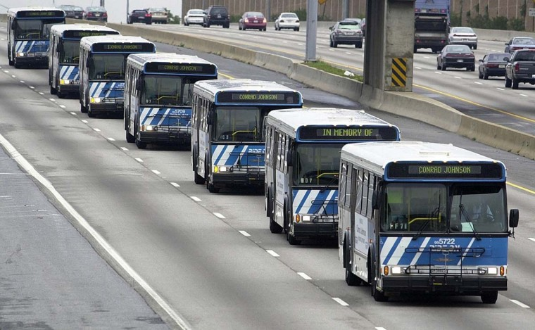 A fleet of buses bearing the name of bus driver Conrad Johnson, the last person gunned down by a sniper in a three-week rampage of shootings in seven jurisdictions, motorcades on the Beltway to Johnson's funeral in Washington, DC, 26 October 2002. Montgomery County prosecutors, where six people were slain, plan to charge US Army veteran John Allen Muhammad, 41, and his companion John Lee Malvo, 17, with the killing spree. (Mike Theiler/AP photo)