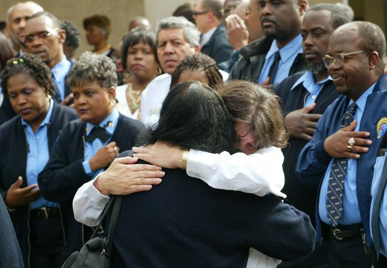 Mourners embrace in front of a group of bus drivers gathered outside the Glendale First Baptist Church in Landover, Md. Saturday, Oct. 26, 2002 during the funeral for bus driver Conrad Johnson, the 35-year-old father gunned down Tuesday in the last of the sniper attacks.(Roberto Borea/AP photo)
