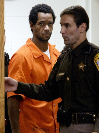 John Allen Muhammad, one of two men accused in a series of sniper attacks in the Washington, DC, area, is escorted to his appearance before Judge Leroy F. Millette at the Prince William County courthouse in Manassas, VA, 13 November, 2002. John Allen Muhammad, 41, and John Lee Malvo, 17, are suspected of terrifying Washington-area residents for three weeks while shooting 13 people as they shopped and pumped gas, killing 10. (Jahi Chikwendiu/Getty Images)