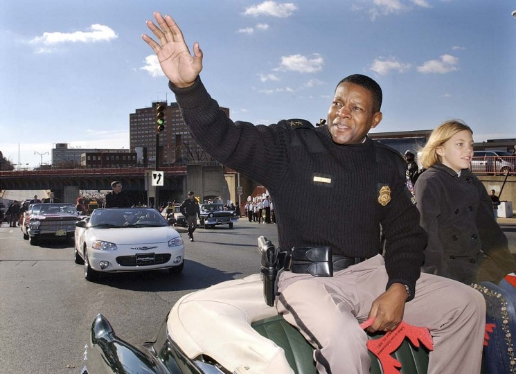 """Montgomery County Police Chief Charles Moose holds foam """"moose"""" antlers while waving during the Thanksgiving Day parade in Silver Spring, Md., Saturday, Nov. 23, 2002. At right is 11-year-old Regan Denchfield, of Chevy Chase, Md., whose father owns and drives the 1948 Cadillac, the parade's lead car. Moose is one of four sniper shooting investigators who participated as grand marshals in the parade. (Ken Lambert/AP photo)"""