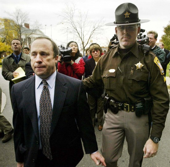 Peter Greenspun, defense attorney for D.C. area sniper suspect John Allen Muhammad, is escorted by a sheriff's deputy as he makes his way back to the Judicial Center in Manassas, Virginia, after speaking with the media November 13, 2002. Muhammad is facing the death penalty if convicted of an October gas station slaying in Manassas. (Kevin Lamarque/Reuters photo)