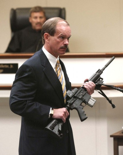 Prince William County prosecutor James Willett handles the weapon used in the sniper shootings during opening arguments of the trial of sniper suspect John Allen Muhammad, at the Virginia Beach Circuit Court in Virginia Beach, Virginia, October 20, 2003. Muhammad, on trial for murder for one of 10 gunshot killings that terrorized the Washington area last year, was allowed to act as his own attorney as opening arguments began on Monday. Judge Leroy Millet, Jr., looks on.(Martin Smith-Rodden/Reuters photo)