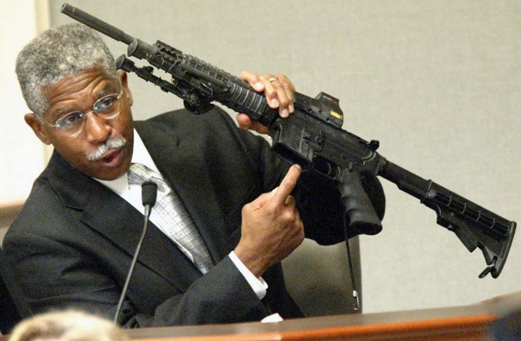ATF agent Walter A. Dandridge Jr., holds the bushmaster rifle used in the sniper shootings during his testimony during his testimony in the trial of sniper suspect John Allen Muhammad in courtroom 10 at the Virginia Beach Circuit Court November 6, 2003 in Virginia Beach, Virginia. Muhammad is on trial in a capital murder case for the shooting death of Dean Meyers, 53-years-old, at a gas station October 9, 2002 in Manassas, Virginia. (Tracy Woodward/Getty Images)