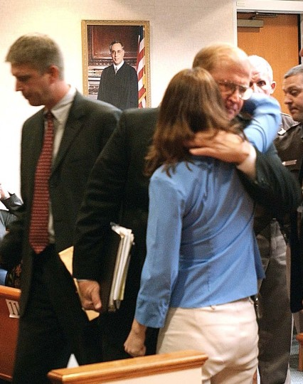 Prince William County Commonwealth Attorney Paul Ebert, center, gives a hug to Katrina Hannum, daughter of sniper victim Linda Franklin, after a jury found John Allen Muhammad guilty on four charges at the Virginia Beach Circuit Court in Virginia Beach, Va., Monday Nov. 17, 2003. (Adrin Snider/AP photo)