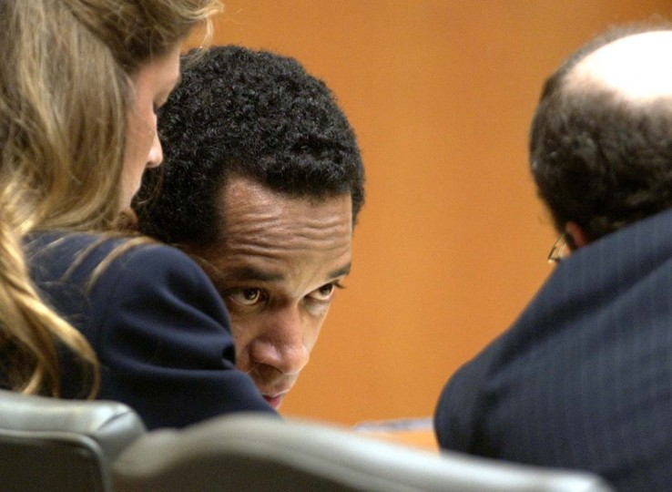 Convicted sniper John Allen Muhammad, center, leans over to talk to his attorney, Peter Greenspun, right, as Christie Leary listens during the penalty phase of his trial in Courtroom 10 at the Virginia Beach Circuit Court in Virginia Beach, Va., Tuesday Nov. 18, 2003. (Dave Ellis/AP photo))