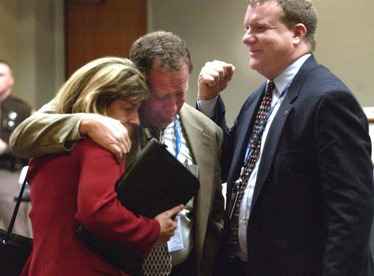 Fairfax County Sniper Task Force supervisor Lt. Bruce Guth, center is comforted by Melissa Thomas, left, and FBI special agent Mike McCoy, right, after the sentence of death was recommended by a jury in the case of convicted sniper John Allen Muhammad at the Virginia Beach Circuit Court in Virginia Beach, Va., Monday Nov. 24, 2003. (Davis Turner/AP photo)