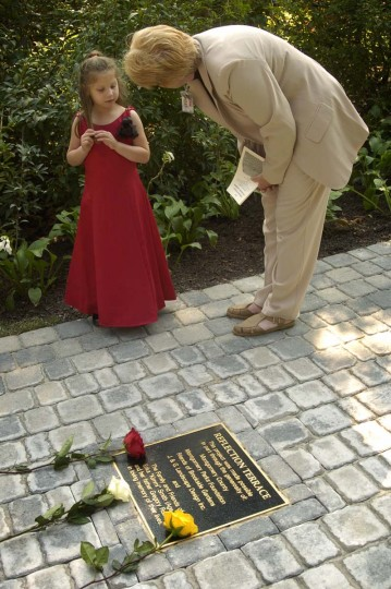 Dedication Ceremony of the Reflection Terrace at Brookside Gardens, in Wheaton Regional Park, in honor of the ten Washington, D.C. area victims of the October 2002 sniper shooting spree. Jocelin Rivera, age 5, studies the plaque on the walkway leading to the Reflection Terrace, while talking with Linda Ridall, civilian employee with the Police Dept., on hand to assist relatives and guests attending the ceremony. (Amy Davis/Baltimore Sun)