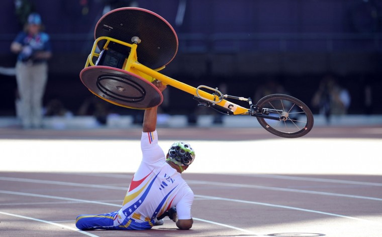 Venezuela's Jesus Aguilar raises his wheelchair after crashing just before the finish line during the men's 800m T53 round 1 during the athletics competition at the London 2012 Paralympic Games in the Olympic Stadium in east London on September 4, 2012. (Glyn Kirk/AFP/Getty Images)
