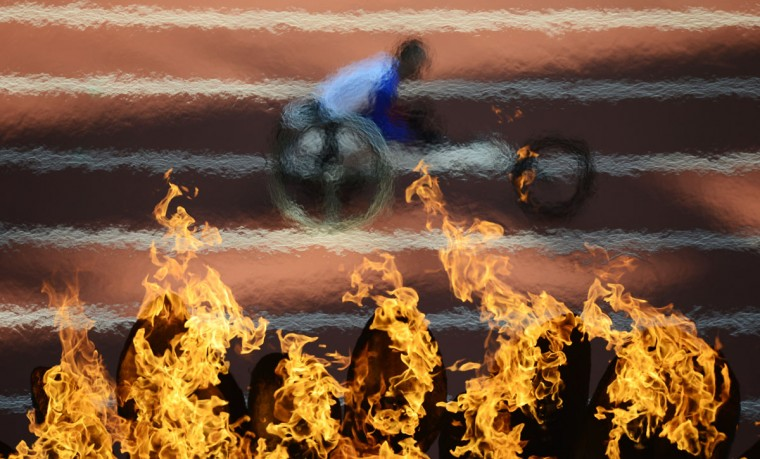 France's Sebastien Mobre takes part in the men's 200m T34 round 1 heat 2 in front of the Paralympic Flame during the athletics competition at the London 2012 Paralympic Games in the Olympic Stadium in east London on September 4, 2012. (Leon Neal/AFP/Getty Images)