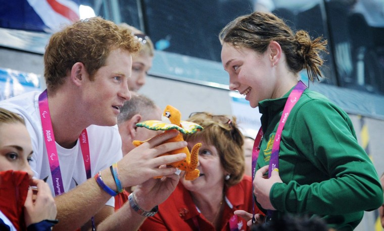 Prince Harry is given a mascot from an Australian Paralympic swimmer on day 6 of the London 2012 Paralympic Games at the Aquatics Centre on September 4, 2012 in London, England. (Stefan Rousseau/WPA Pool/Getty Images)