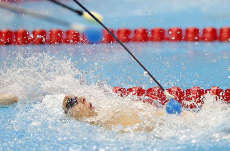 A coach uses a stick with a soft end to let Yang Bozun of China know that he is reaching the end of the pool during the men's 100m Backstroke S11 swimming final at the London 2012 Paralympic games at the Olympic Park in Stratford in London, September 2, 2012. The S11 category is for the visually impaired. (Andrew Winning/Reuters)