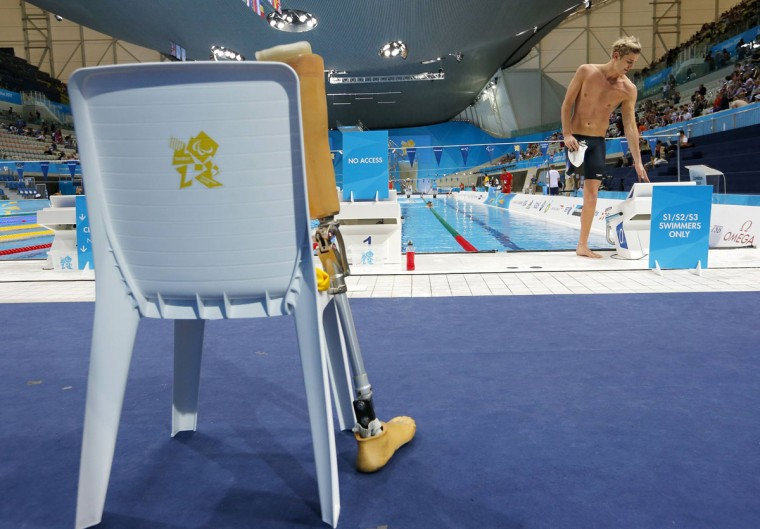 Brendan Hall of Australia steadies himself after a training swim as his prosthetic leg leans against a race officials' chair on the third day of the London 2012 Paralympic games at the Olympic Park in Stratford in London, September 1, 2012. (Andrew Winning/Reuters)
