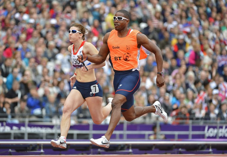 Libby Clegg of Britain (L) and her guide Mikail Huggins run during the Women's 100m T12 classification heat at the Olympic Stadium during the London 2012 Paralympic Games September 1, 2012. Clegg set a world record in her heat, which lasted seven minutes before being beaten in the following heat. In the T12 category the competitors are partially sighted and can have a guide when competing, but must cross the finish line ahead of their guide. (Toby Melville/Reuters)