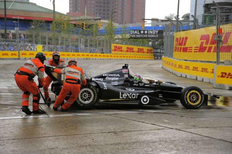 Track officials work to move Dario Franchitti's Honda, which wiped out during a light shower at Turn One.