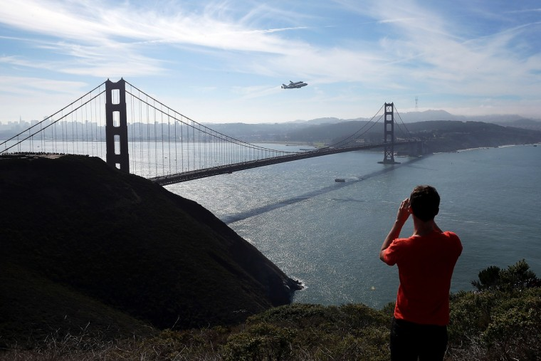 A spectator takes a photo of the Space Shuttle Endeavour as it flies on top of a modified 747 jumbo jet over the Golden Gate Bridge while traveling to Los Angeles . The Space Shuttle Endeavour did a 4-1/2 hour tour over California landmarks before heading to Los Angeles International Airport where it will be prepared to be moved to its new permanent home at the California Science Center in downtown Los Angeles. The shuttle will be on public display starting October 30. (Justin Sullivan/Getty Images)