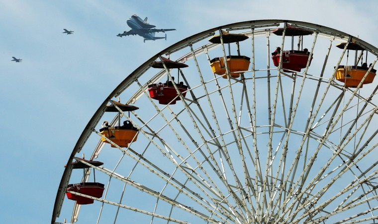 Space shuttle Endeavour, sitting on top of NASA's Shuttle Carrier Aircraft or SCA, flies over the ferris wheel on Santa Monica Pier atop it's transport plane on September 21, 2012 in Santa Monica, California. The Space Shuttle Endeavour will be placed on public display at the California Science Center. This is the final ferry flight scheduled in the Space Shuttle Program era. (Stephen Dunn/Getty Images)