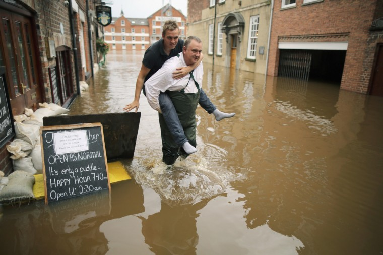 A man carries a a friend through floodwaters as the swell of the River Ouse flows through the city of York in York, England. Heavy wind and rain have battered central and northern parts of the UK with more rain forecast. Swollen rivers are still threatening towns across Britain as rain water from hills makes it's way down. (Christopher Furlong/Getty Images)
