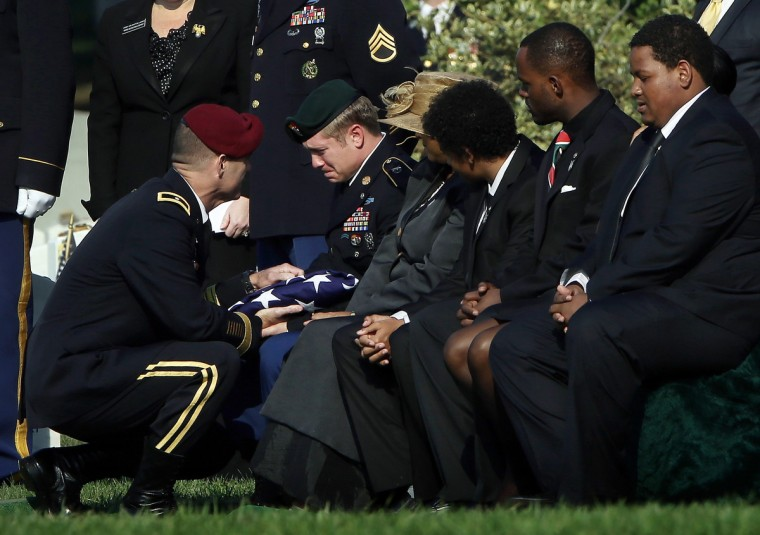 During a burial service for U.S. Army Chief Warrant Officer 2 Thalia S. Ramirez, Brigadier Gen. Charles Flynn (L) presents the American flag that covered her casket to Ramirez's husband, U.S. Army Sgt. Jesse Belbeck (2nd L) at Arlington National Cemetery in Arlington, Virginia. Ramirez died September 5 in Logar Province, Afghanistan, from injuries suffered when a OH-58D Kiowa helicopter crashed. (Win McNamee/Getty Images)