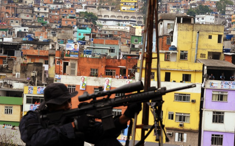 A Brazilian police sharp-shooter secures a position atop a school building in front of the Rocinha shantytown, where Rio de Janeiro's government started the installation of the Pacifier Police Unit (UPP) project. Brazilian authorities stepped up a pacification drive in Rio's largest shantytown Thursday, nearly doubling the police presence in a hillside favela overlooking the city's most famous beaches. (Antonio Scorza/GettyImages)