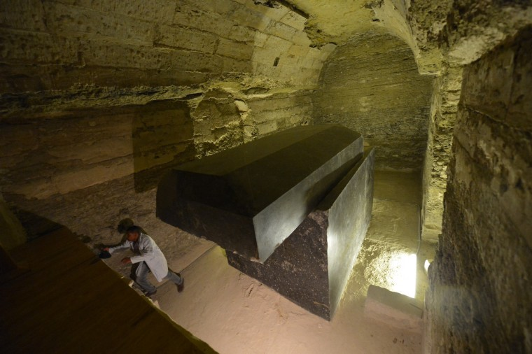 An Egyptian archeologist walks next to a tomb at the Serapeum of Saqqara, a vast underground necropolis south of Cairo dedicated to the bulls of Apis, as it reopens to the public after 11 years of renovation. The Serapeum, whose origin dates back to around 1400 BC, was discovered in 1851 by French Egyptologist Auguste Mariette, founder of the first department of Egyptian antiquities. The site contains huge subterranean galleries in which are contained the large tombs of some 30 sacred bulls, accompanied by steles bearing inscriptions providing information on the reigns under which the animals lived. (Khaled Desouki/GettyImages)