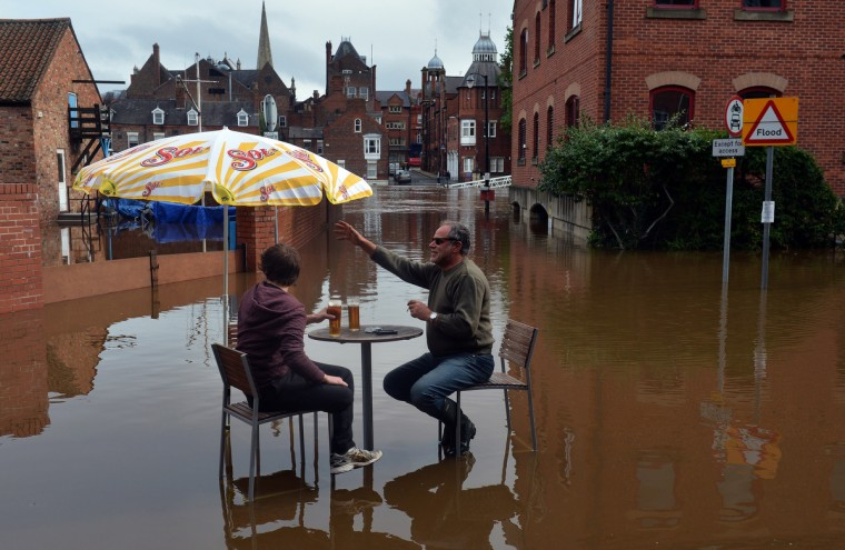 Men sit in flood waters outside a bar as water levels continue to rise on the River Ouse in York, northern England. Britain was bracing for more torrential rain as hundreds of people spent the night away from their flooded homes following two days of heavy downpours. (Paul Ellis/GettyImages)