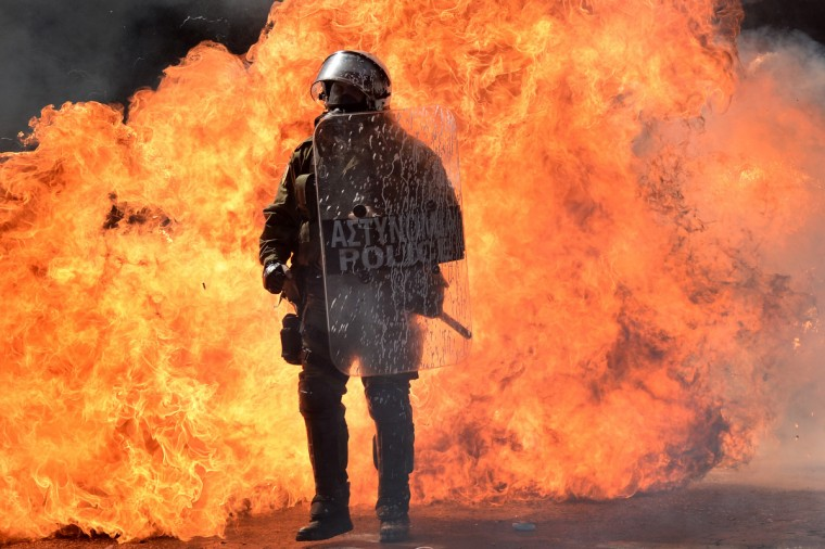 A riot police officer stands in front of burning firebombs in Athens during a 24-hours general strike. Police in Athens clashed with hooded youths throwing firebombs on the sidelines of a large demonstration against a new round of austerity cuts. (Aris Messinis/GettyImages)