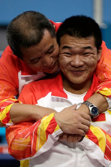 Gold medal winner Qi Feng of China is congratulated by his coach Weipo Li during the medal ceremony of the Men's -52 kg Powerlifting on day 2 of the London 2012 Paralympic Games at ExCel on August 31, 2012 in London, England. (Matthew Lloyd/Getty Images)
