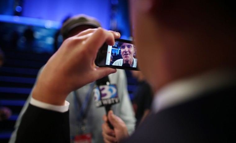 A man photographs musician James Taylor using an Apple iPhone as he gives an interview during the final day of the Democratic National Convention at Time Warner Cable Arena on September 6, 2012 in Charlotte, North Carolina. (Chip Somodevilla/Getty Images)