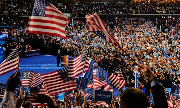 People wave American flags as Democratic presidential candidate, U.S. President Barack Obama speaks on stage to accept the nomination for president during the final day of the Democratic National Convention at Time Warner Cable Arena on September 6, 2012 in Charlotte, North Carolina. The DNC, which concludes today, nominated U.S. President Barack Obama as the Democratic presidential candidate. (Kevork Djansezian/Getty Images)