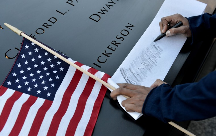 Alicia Watkins, of Washington, DC, makes a rubbing of a friend's name at the South Pool during memorial ceremonies for the eleventh anniversary of the terrorist attacks on lower Manhattan at the World Trade Center site September 11, 2012 in New York City. (Justin Lane-Pool/Getty Images)