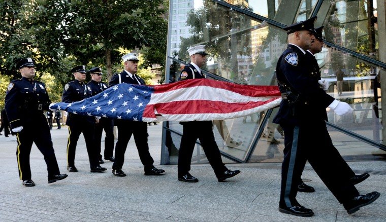 Port Authority Police Officers carry an American flag that flew over at the World Trade Center towers during memorial ceremonies for the eleventh anniversary of the terrorist attacks on lower Manhattan at the World Trade Center site September 11, 2012 in New York City. (Justin Lane-Pool/Getty Images)