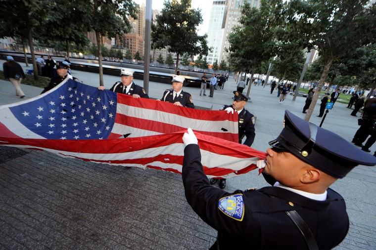 Fire and police officers hold a large American flag before the start of the memorial ceremonies for the eleventh anniversary of the terrorist attacks on lower Manhattan at the World Trade Center site September 11, 2012 in New York City. (Todd Maidel-Pool/Getty Images)