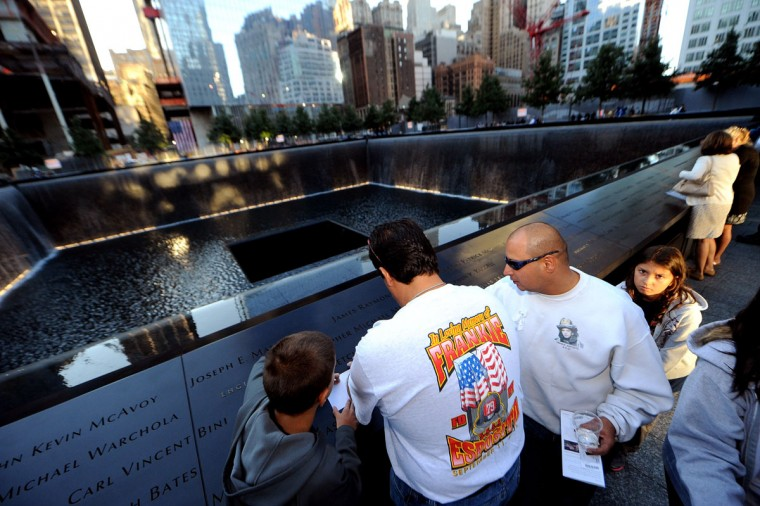 People take a rubbing of a name of a loved-one inscribed on one of the reflecting pools before the start of the memorial ceremonies for the eleventh anniversary of the terrorist attacks on lower Manhattan at the World Trade Center site September 11, 2012 in New York City. (Todd Maidel-Pool/Getty Images)