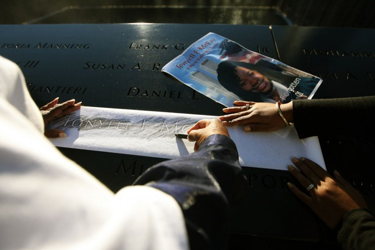 The family of Tonyell McDay of Colonia, NJ rubs her name inscribed on the north tower memorial before the start of the memorial ceremonies for the eleventh anniversary of the terrorist attacks on lower Manhattan at the World Trade Center site September 11, 2012 in New York City. (Chris Pedota-Pool/Getty Images)