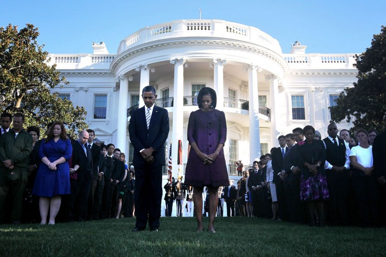 U.S. President Barack Obama (L) and first lady Michelle Obama (R) observe a moment of silence with White House staff to mark the 11th anniversary of the 9/11 attacks September 11, 2012 at the South Lawn of the White House in Washington, DC. (Alex Wong/Getty Images)