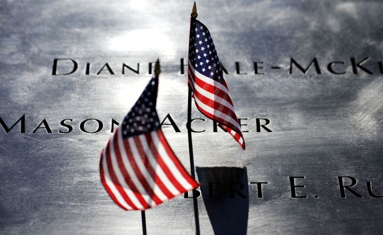 American flags are sit in the engravings of people's names during memorial ceremonies for the eleventh anniversary of the terrorist attacks on lower Manhattan at the World Trade Center site September 11, 2012 in New York City. (Justin Lane/Getty Images)