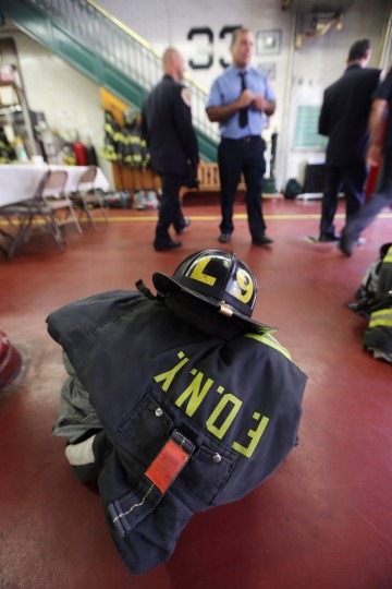 New York City firefighters gather at Engine 33, Ladder 9 between ceremonies for the eleventh anniversary of the terrorist attacks on lower Manhattan at the World Trade Center on September 11, 2012 in New York City. Engine 33, Ladder 9 lost ten firefighters in the attacks. (Mario Tama/Getty Images)